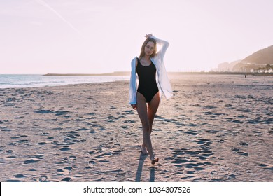 Attractive and pretty, beautiful young model with blonde hair wears trendy hipster outfit for day on beach, amazing stylish blogger lifestyle. Travels around and enjoys youth and freedom.