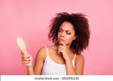 Attractive, pretty, charming, thoughtful, unhappy, sad girl looking at comb in hand touching chin with finger, having dry, oiled hair loss, she need mask, lotion, balm, isolated on pink background