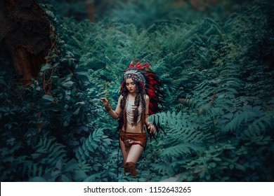 Attractive pretty Indigenous American Indian walks in thickets of dark jungles. Princess Pocahontas. Girl in a leather suit of ethnic hunters. Artistic Photography.