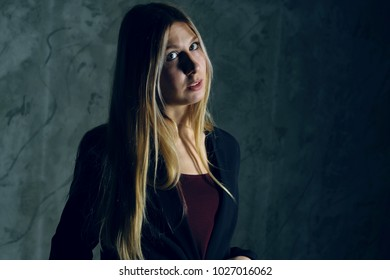 Attractive pretty young model posing against a dark studio background with copy space looking. Atomic blonde woman. Fashion style