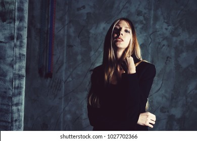 Attractive pretty young model posing against a dark studio background with copy space looking. Atomic blonde woman. Cold cinematic style