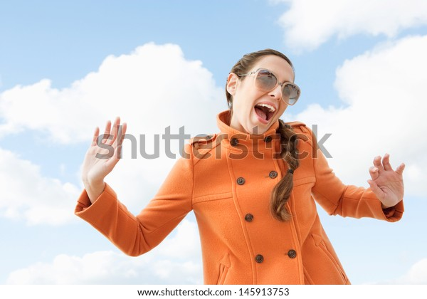Attractive quirky individual woman shouting and holding her arms in the air with a humorous fun expression against a blue sky with clouds, outdoors.