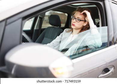 Attractive red hair businesswoman stuck in a traffic jam.Running late to work.