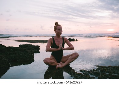 Attractive red hair woman practicing yoga on the coast of Indian ocean in a black swimsuit during sunset, Indonesia, Bali