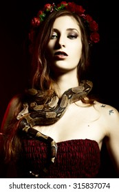 Attractive red haired woman posing with boa constrictor
