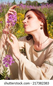 Attractive red-hair woman in traditional dress relaxes with flowers on fireweed meadow