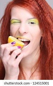 attractive redhaired woman biting the lemon