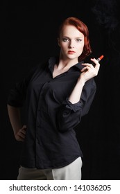 Attractive red-haired young woman holding lipstick like a cigar. Studio shot