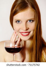 The attractive red-haired young woman with a red wine glass