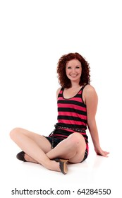 Attractive red-haired young woman sitting cross-legs with the hands against the floor, dressed with a striped T-shirt, . Smiling at camera. Studio shot. White background