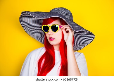 Attractive red-haired young woman in sunglasses in form of heart and striped white and black hat on yellow summer background. Sexy stylish model enjoying sun.