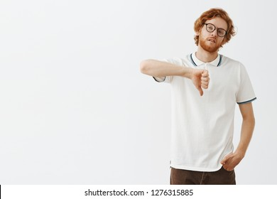 Attractive redhead male snob in glasses and casual outfit tilting head looking left with indifference being unimpressed and careless to situation showing thumbs down expressing dislike and boredom