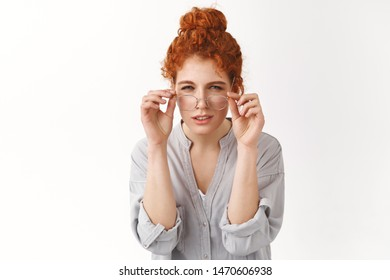 Attractive redhead woman with curly hair combed in bun have sight problems, bad vision, put-on glasses, squinting cannot read what written on sign, staring focused camera, white background