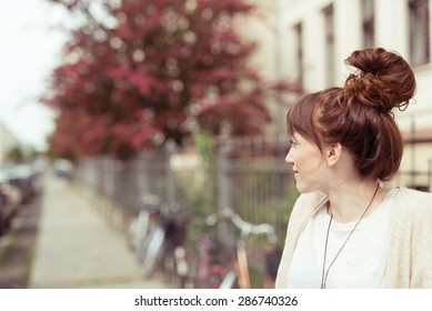 Attractive redhead woman with a fun hairstyle with her long hair wound into a high bun or top knot standing in an urban street, profile view with copyspace