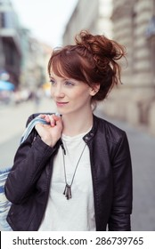 Attractive redhead woman with her hair in a bun standing holding a bag over her shoulder in an urban street looking to the side with a serious expression