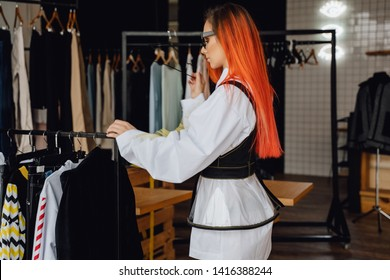 Attractive Redhead Woman in Showroom Side View. Young Beauty Choosing Trendy Apparel. Pretty Caucasian Redhead Looking at Rack with Designer Clothes Collection. Commercial Catalog Shoot