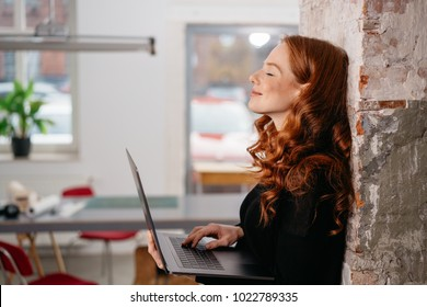 Attractive redhead woman standing daydreaming as she leans against a brick wall in an office holding an open laptop