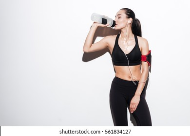 Attractive relaxed young woman with armband drinking water and listening to music over white background