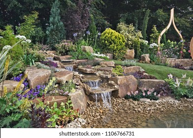 An attractive rock garden with waterfall into a water featured pool with plants and flowers