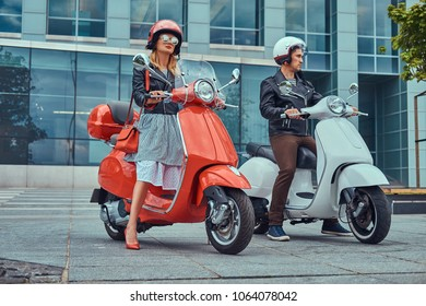 Attractive romantic couple, a handsome man and sexy female, standing with two retro Italian scooters against a skyscraper.