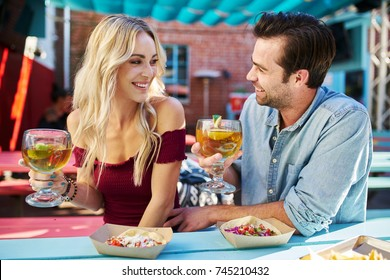 attractive romantic couple holding beers at mexican restaurant about to eat tacos
