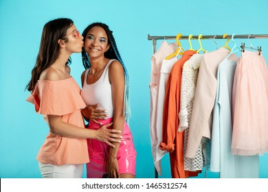 Attractive romantic lesbian couple on picture. Young georgian woman kissing cheek her african girlfriend. LGBT rights. Free love. Isolated over blue background