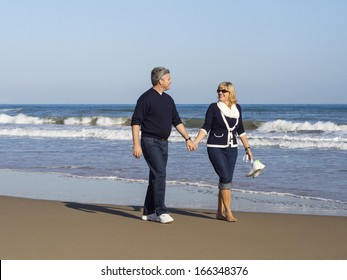 Attractive romantic mature couple walking along the beach hand in hand at the edge of the sea enjoying the beauty of the seaside and tranquillity of nature