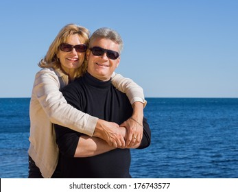 Attractive romantic middle-aged mature man and woman wearing sunglasses standing in the sunshine enjoying the seaside in an affectionate embrace