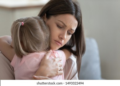 Attractive sad woman embraces little frustrated girl rear view, daughter snuggle to mother seeking for support and protection, concept of empathy and consoling or people make peace after scold concept