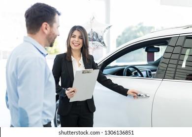 Attractive sales worker opening car door for mid adult client in showroom