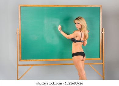 An attractive school teacher in front of a chalkboard.