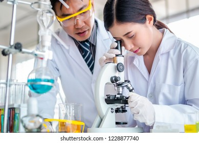 Attractive scientist looking sample with microscope at laboratory with lab glassware background. Science or chemistry research and development concept.