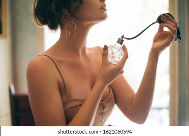 attractive seductive sensual stylish woman in boho dress sitting vintage retro cafe holding perfume