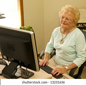 Attractive senior adult female working happily at her PC
