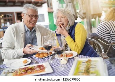 Attractive senior couple eating tapas outdoors