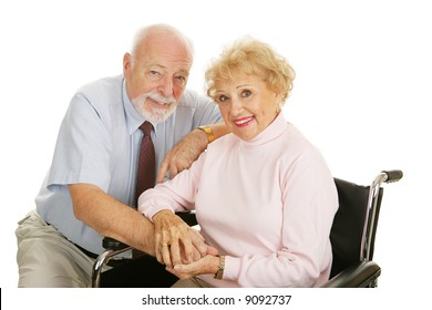 Attractive senior couple - the wife is in a wheelchair.  Isolated on white.