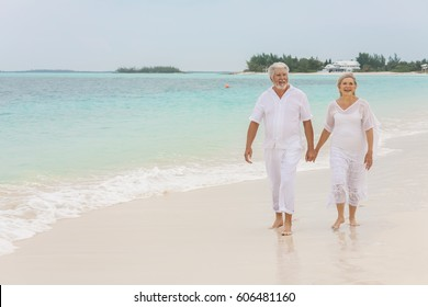 Attractive senior male and female Caucasian couple in white casual clothes walking on a tropical vacation beach