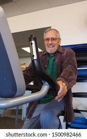 Attractive senior man at gym riding a stationary bike as physical therapy