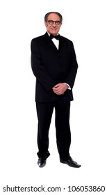 Attractive senior man posing in tuxedo isolated over white background