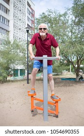 Attractive senior man trains on sporting equipment in a city in the open air. Available sports equipment in a public place.