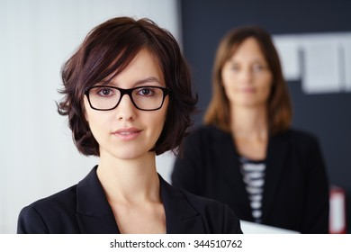 Attractive senior partner or manageress wearing glasses posing in front of her colleague in an office, close up head and shoulders portrait