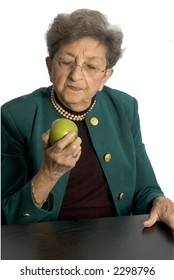 attractive senior woman  about to eat granny smith apple business executive with pearls