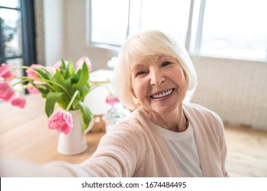 Attractive senior woman cooking on kitchen. Cheerful grandmother baking and making selfie on a smart phone