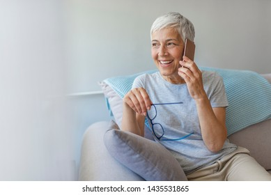 Attractive senior woman in eyeglasses talking on smartphone. Portrait of mature woman talking on phone. Portrait of woman sitting on sofa at home with mobile phone