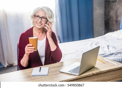 Attractive senior woman in eyeglasses talking on smartphone and holding paper cup