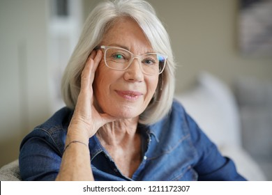 Attractive senior woman at home with eyeglasses