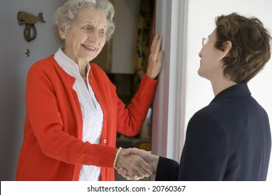 Attractive senior woman shaking hands with visitor at her front door