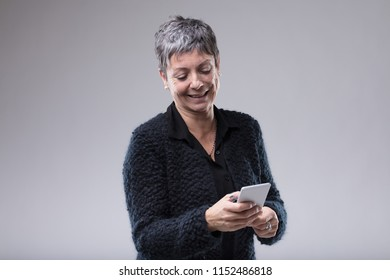 Attractive senior woman typing an sms or text message on her mobile phone with a smile of pleasure over grey with copy space
