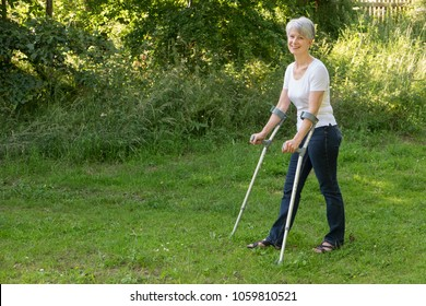 Attractive senior woman walking with crutches