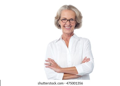 Attractive senior woman wearing glasses posing with folded arms.